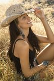 Young woman wearing a straw cowboy hat. Mid-adult Caucasian woman sitting in field wearing straw cowboy hat Royalty Free Stock Image