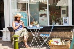 Young woman wearing straw cowboy hat sitting outside a shop wind. Leek, Staffordshire Moorlands, England, U.K - June 21 2014 : Young woman wearing straw cowboy Royalty Free Stock Photos