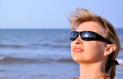 Young woman wearing a sunglass. Es reflecting the beach. sun and an umbrella Royalty Free Stock Photography