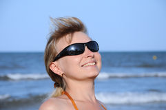 Young woman wearing a sunglasses 2. Young woman wearing a sunglasses reflecting the beach. sun and an umbrella Royalty Free Stock Photos
