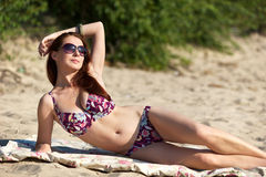 Young woman wearing sunglasses on the beach Royalty Free Stock Images