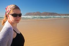 Young woman wearing sunglasses on the beach at Muizenberg. Young adult woman wearing sunglasses and a black top with a white jersey standing on the beach looking Stock Image