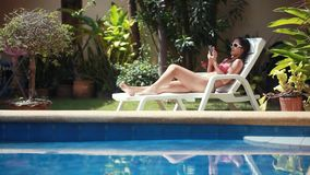 Young woman wearing sunglasses and bikini using smartphone lying on sunbed by pool. 1920x1080, hd stock video footage
