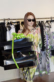 Young woman wearing sunglasses while carrying boxes in fashion boutique Stock Images