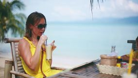 Young woman wearing sunglasses drinking cocktail in summer and enjoying her vacation in beach cafe on sea as a. Young blonde woman drinking cocktail in summer stock video