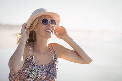 Young woman wearing sunglasses and hat at beach. During sunny day Royalty Free Stock Image