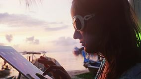 Young woman wearing sunglasses in outdoor cafe on the shore at sunset uses tablet computer and having drink. Vacation. Young woman wearing sunglasses in outdoor stock video