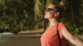 Young woman wearing sunglasses relaxing on a tropical beach. Beautiful woman in pure happiness with arms raised outstretched up. Close up side portrait of a stock video footage