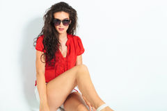 Young woman wearing sunglasses and sitting on the floor with leg Royalty Free Stock Photos