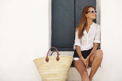 Young woman wearing sunglasses sitting on steps looking away Royalty Free Stock Image