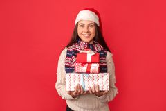 Celebration Concept. Young woman in scarf and santa hat standing isolated on red with gift boxes smiling cheerful royalty free stock photography