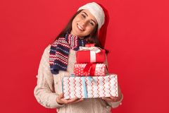Celebration Concept. Young woman in scarf and santa hat standing isolated on red with gift boxes smiling joyful close-up royalty free stock images