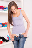 Young woman wearing or takes off jeans. Waist up of beautiful brunette wearing jeans and smiling Royalty Free Stock Photos