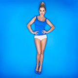 Young Woman Wearing Tank Top With Hand On Waist. On Blue Background Stock Photos
