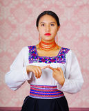 Young woman wearing traditional andean dress, facing camera doing sign language word for until Stock Image