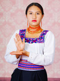 Young woman wearing traditional andean dress, facing camera doing sign language word Stock Image