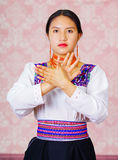 Young woman wearing traditional andean dress, facing camera doing sign language word Royalty Free Stock Photos