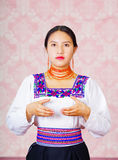 Young woman wearing traditional andean dress, facing camera doing sign language word for accounting Stock Image
