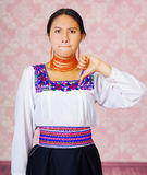 Young woman wearing traditional andean dress, facing camera doing sign language word for bad Stock Image