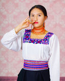 Young woman wearing traditional andean dress, facing camera doing sign language word for boy Royalty Free Stock Photo