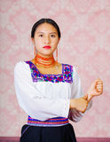 Young woman wearing traditional andean dress, facing camera doing sign language word for brother Stock Photography