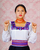 Young woman wearing traditional andean dress, facing camera doing sign language word for can Stock Images