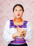 Young woman wearing traditional andean dress, facing camera doing sign language word for careful Stock Image