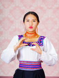 Young woman wearing traditional andean dress, facing camera doing sign language word for communicate Stock Photos