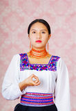 Young woman wearing traditional andean dress, facing camera doing sign language word for debt Royalty Free Stock Photo