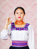 Young woman wearing traditional andean dress, facing camera doing sign language word for emergency Royalty Free Stock Photo