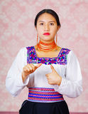 Young woman wearing traditional andean dress, facing camera doing sign language word for far Royalty Free Stock Photo