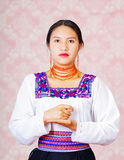 Young woman wearing traditional andean dress, facing camera doing sign language word for fee Stock Photos