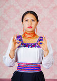 Young woman wearing traditional andean dress, facing camera doing sign language word for formulate Royalty Free Stock Photo