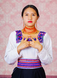 Young woman wearing traditional andean dress, facing camera doing sign language word for freedom Royalty Free Stock Image