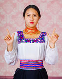 Young woman wearing traditional andean dress, facing camera doing sign language word for freedom Stock Image