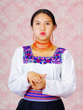 Young woman wearing traditional andean dress, facing camera doing sign language word for full Stock Images