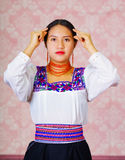 Young woman wearing traditional andean dress, facing camera doing sign language word for graduated Stock Photo