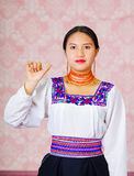 Young woman wearing traditional andean dress, facing camera doing sign language word for hello Royalty Free Stock Photo