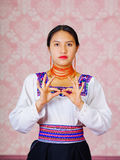 Young woman wearing traditional andean dress, facing camera doing sign language word for important Stock Photography