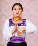 Young woman wearing traditional andean dress, facing camera doing sign language word for later Royalty Free Stock Photo
