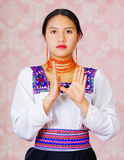 Young woman wearing traditional andean dress, facing camera doing sign language word for later Royalty Free Stock Photography