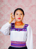 Young woman wearing traditional andean dress, facing camera doing sign language word for listening Stock Photos
