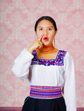 Young woman wearing traditional andean dress, facing camera doing sign language word for man Royalty Free Stock Images