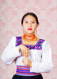Young woman wearing traditional andean dress, facing camera doing sign language word for meter Royalty Free Stock Photography