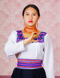 Young woman wearing traditional andean dress, facing camera doing sign language word for municipality Royalty Free Stock Photos
