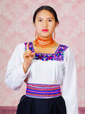 Young woman wearing traditional andean dress, facing camera doing sign language word for need Stock Photos