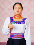 Young woman wearing traditional andean dress, facing camera doing sign language word for need Royalty Free Stock Photo