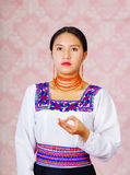 Young woman wearing traditional andean dress, facing camera doing sign language word for pain Stock Image