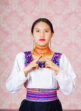 Young woman wearing traditional andean dress, facing camera doing sign language word for recognize Stock Photo