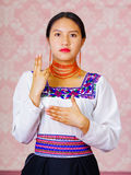 Young woman wearing traditional andean dress, facing camera doing sign language word for son Royalty Free Stock Photography